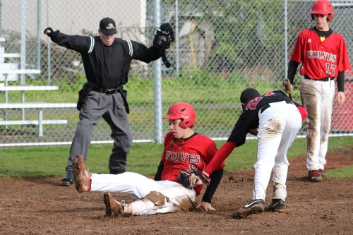 A muddy (but safe) Aaron Trumbull slides across home.