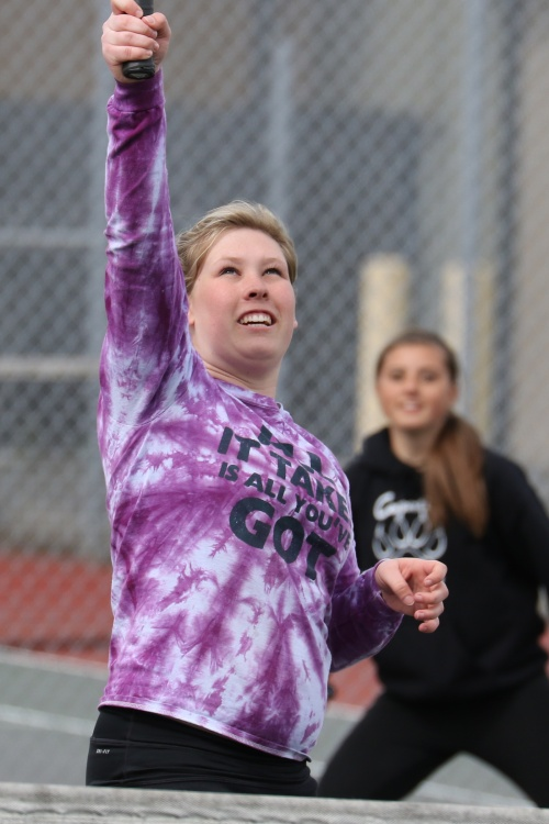 Sydney Autio reaches up for an overhead, while doubles partner Micky LeVine lurks in the background.