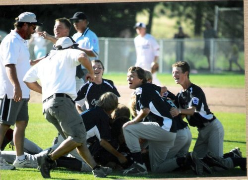 Coach Chris Tumblin (left) charges in to join the dog pile after Central Whidbey won the state title in 2010.