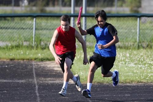 Sean Toomey-Stout (in red) and Nick Wielandt work on their relay hand-offs. (Fisken photo)