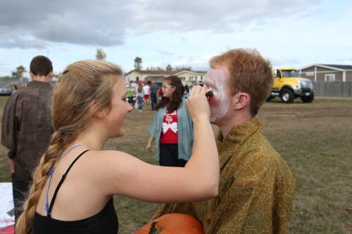 Allison Wenzel works on Jesse Hester's makeup, before they join the Mulan float.